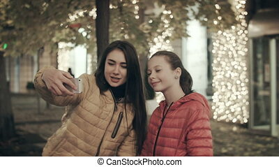 Two beautiful girls of different ages do selfie on the phone at night in the city with lights.