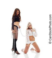 Two beautiful girls posing with chain in studio