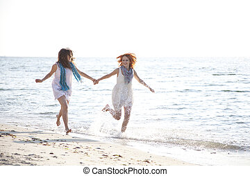 Two beautiful girls running on the beach.