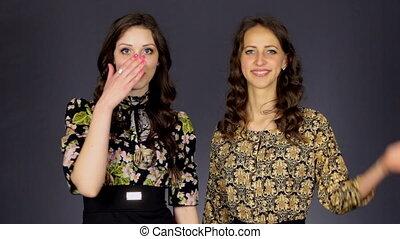Two beautiful girls send an air kiss
