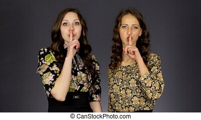 Two beautiful girls show silent sign and send a kiss, synchronously move