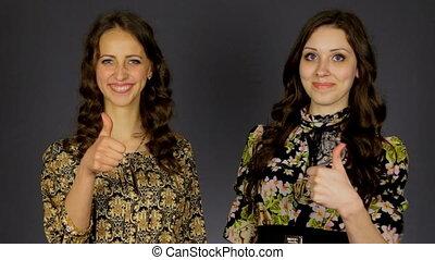 Two beautiful girls show thumb good,