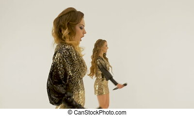 Two beautiful girls sing and dance in the studio, on a white background. Mounting a music video.