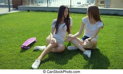 Two beautiful girls sitting on the grass
