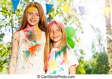 Two beautiful girls smeared with colored powder