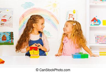 Two beautiful girls stacking blocks