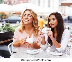 Two beautiful girls with cups chatting in summer cafe