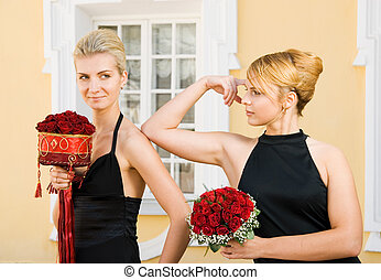 Two beautiful girls with flowers in black evening dresses