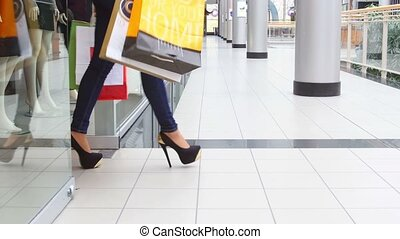Two beautiful girls with shopping bags come out of the store in the mall.