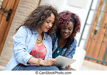 Two beautiful girls with tablet computer in urban background