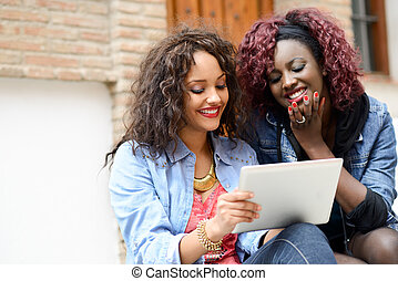 Two beautiful girls with tablet computer in urban background...