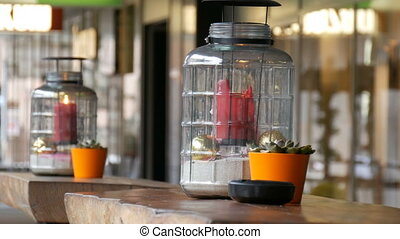 Two beautiful glass candlestick with a big red burning wax candle of red color which is inside the candlestick and stands on the table of the street cafe