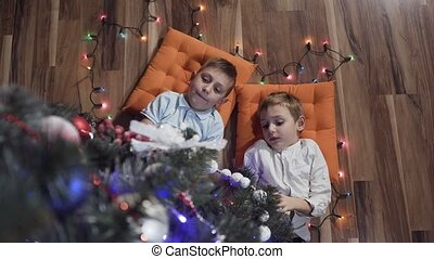 Two beautiful kids are lying happy on the pillows near the Christmas tree