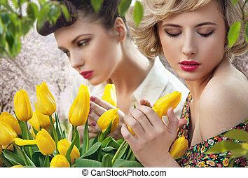 Two beautiful ladies in a tulip garden