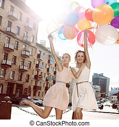 two beautiful girls in white and pink dresses holding bunches of multicolored balloons in the street