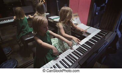 Two beautiful little girls are playing piano in a room