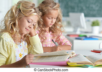 two beautiful little girls at class read book and writing at...