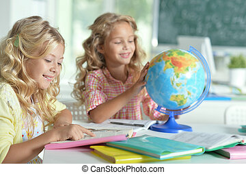 two beautiful little girls at class reading book and looking...