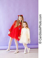 Two beautiful little girls in red and white dresses for the holiday