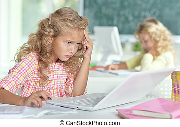 Two beautiful little girls working with computers at class