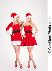 Two beautiful positive women in red santa claus dresses posing