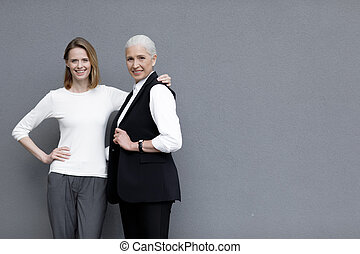 Two beautiful smiling women standing together, young and senior people