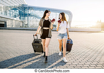Two beautiful smiling young asian brunette girls walking with travel suitcases on wheels and passports with tickets in their hands, on the modern airport background. Travel, air flights concept