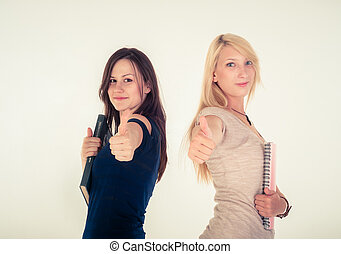 Two beautiful student girls showing thumbs up