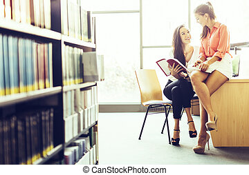 Two beautiful students studying in the library