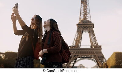 Two beautiful traveling female taking photos on smartphone...