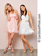 two beautiful woman in chic dresses.