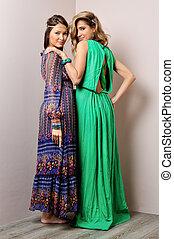 Two beautiful woman in long dresses.