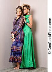 Two beautiful woman posing in a fancy dresses
