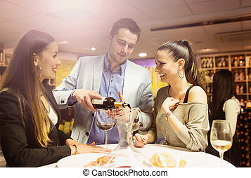 Two beautiful woman - Two beautiful women and a waiter in a...