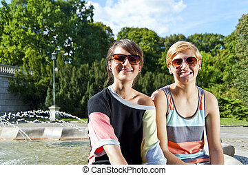 Two  beautiful woman with sunglasses on park