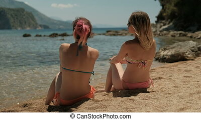 Two beautiful women are sitting on a sunny beach and talking. Attractive ladies rest on the sand.