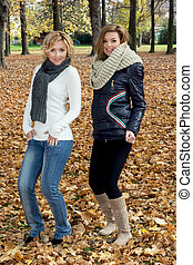 Two beautiful women dancing in the autumn park.