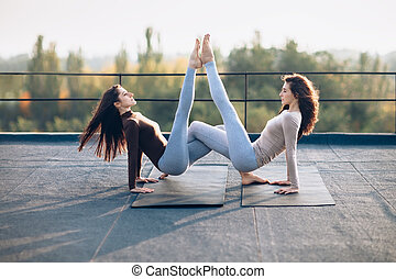 Two beautiful women doing acroyoga asana on the roof...