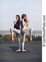 Two beautiful women doing yoga asana on the roof outdoors