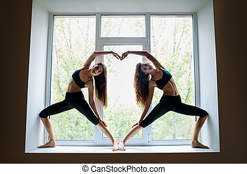 Two beautiful women doing yoga asana showing heart symbol on...