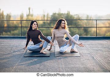 Two beautiful women doing yoga asana virabhadrasana on the roof outdoor