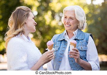 Two beautiful women eating ice cream and having fun.