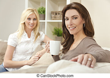 Two Beautiful Women Friends Drinking Tea or Coffee at Home