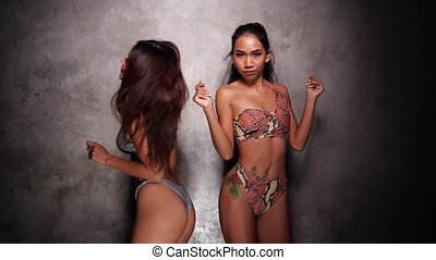Two beautiful Asian girls in bikini dancing sensually over concrete wall background in the studio - video in slow motion