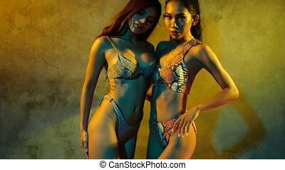 Two beautiful Asian girls in bikini posing sensually over concrete wall background in the studio - video in slow motion