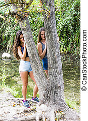 Two beautiful women in nature on the bank of a mountain river