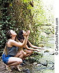 Two beautiful women in nature, splashing water in a river of a mountain river