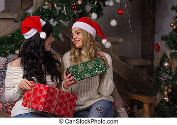 Two beautiful women in santa hats smiles exchange gifts for Christmas