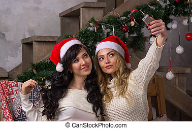 Two beautiful women in santa hats smiles make selfies near of Christmas tree.