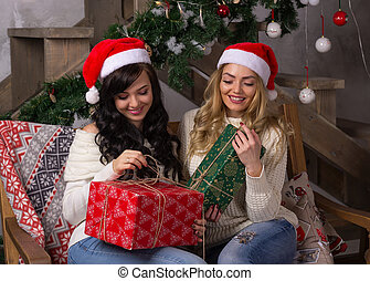 Two beautiful women in santa hats smiles unfold gifts for Christmas.
